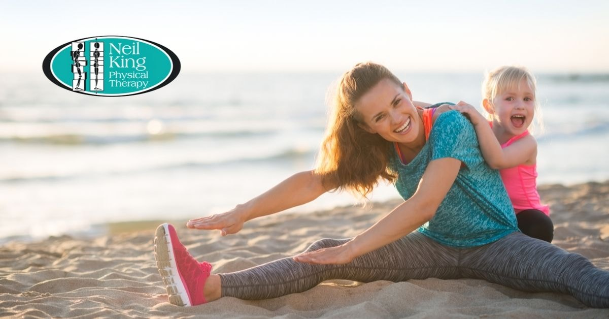 Woman Stretching on Beach with Daughter - Physical Therapy Near Shelby Charter Township - Neil King Physical Therapy