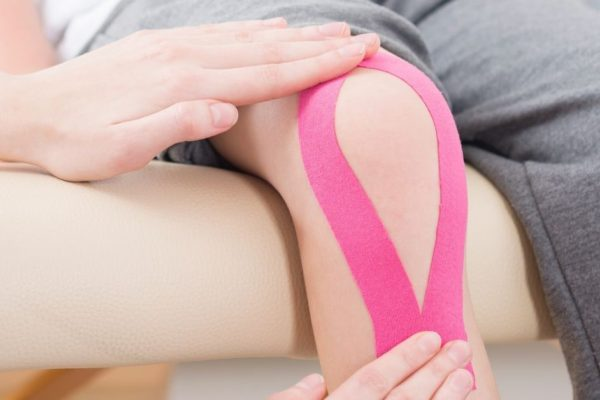 Pink Kinesio Tape On Knee - Neil King Physical Therapy