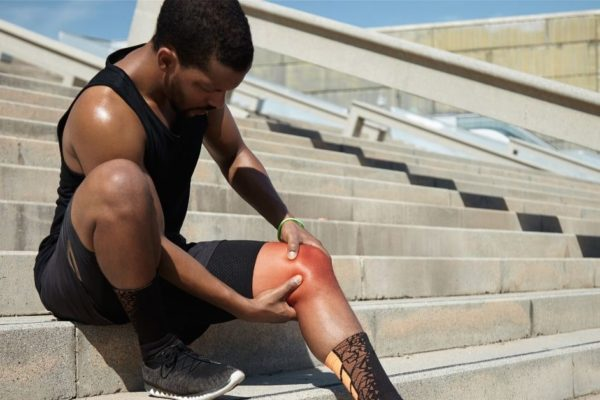 Man with Knee Pain Sitting on Bleachers - Neil King Physical Therapy